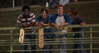 Members of Lee High School's Class of '77 (including a young Ben Affleck) eagerly await the conclusion of a Little League game with custom-made paddles in hand.