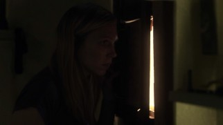 Bright sunlight creeps in a crack at the door as Kim (Amy Cale Peterson) takes a peek at the outside world she hasn't experienced in six months.