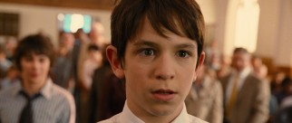 Public embarrassment strikes Greg Heffley (Zachary Gordon) on his way up to receive communion at a weekly church service.