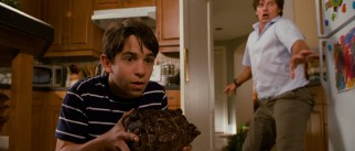 Greg Heffley (Zachary Gordon) and his father (Steve Zahn) use Mom's pot roast to lure the family's new dog Sweetie away from Manny's blanket Tingy.