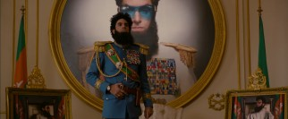 Admiral General Aladeen (Sacha Baron Cohen) stands proudly in a room designed to his specifications.