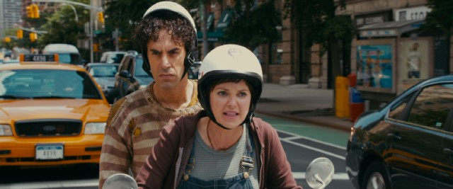 Taking Aladeen (Sacha Baron Cohen) for a dissident, bleeding heart liberal Zoey (Anna Faris) gives him a ride on her Vespa.