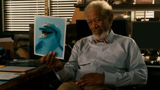 Prosthetics doctor Cameron McCarthy (Morgan Freeman) holds up a photo of his newest patient (Winter the dolphin).