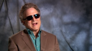 Albert Brooks hides his missing eyebrows with sunglasses in a featurette interview.