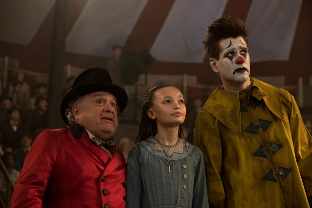 Max Medici (Danny DeVito), Milly (Nico Parker), and fireman clown Holt Farrier (Colin Farrell) watch as Dumbo takes flight.