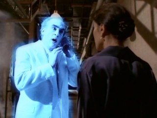 A glowing blue Jake Marley (Jeffrey DeMunn) gets directions on his 1990s-sized cellular telephone.