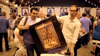 Fans at a convention show their love of Star Wars in an original trilogy poster they will get signed.