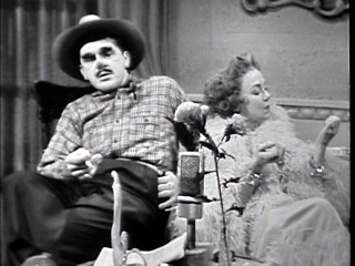 A working-class man (Ernie Kovacs) appears on the talk show of self-absorbed Zaza Esterhazy (Edie Adams) in a January 1956 episode.