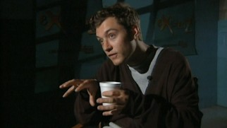 A young Jude Law talks games and society with a Styrofoam cup in hand.