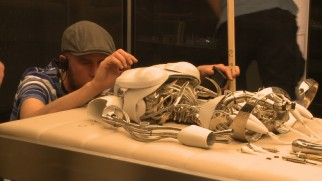 A crew member makes sure this robotic skeleton wreckage is just right in one of nine behind-the-scenes vignettes.
