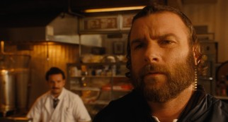 Hasidic police officer Dovi (Liev Schreiber) grows suspicious of Murray, while Max Casella works a counter in the background.