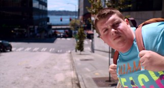 "Troy (Jacob Wysocki) peeks his head out in advance of an oncoming bus in ""Fat Kid Rules the World."""