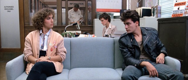 At the Shermer Police Station, Jeanie Bueller (Jennifer Grey) makes the acquaintance of a tired-looking young man (Charlie Sheen).