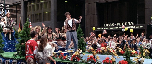 "Ferris Bueller surprises his friends by leading a German-American parade float in a rousing lip-synching of Wayne Newton's ""Danke Shoen."""