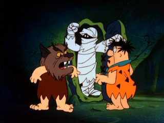"Fred and Barney in a werewolf mask open the door for a mummy attack (by Wilma) in ""Rockula and Frankenstone."""