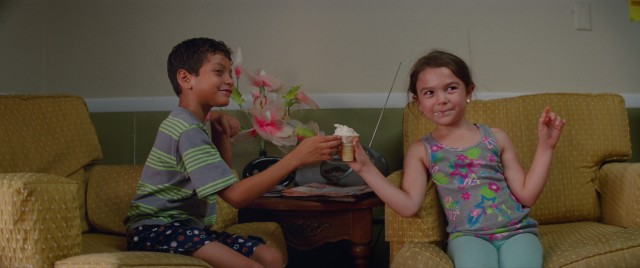"Scooty (Christopher Rivera) and Moonee (Brooklynn Kimberly Prince) eat an ice cream cone bought for them by tourists inside the Magic Castle motel in ""The Florida Project."""