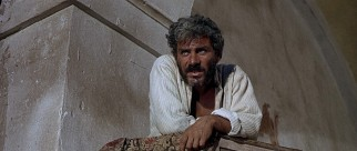 From a pulpit in an abandoned church, El Indio (Gian Maria Volonté) preaches to his bandits about the El Paso bank they are to rob.