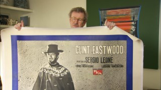 "Christopher Frayling shows off one of his many beloved ""For a Few Dollars More"" posters."