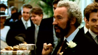 Gareth (Simon Callow) puts his card on a more impressive wedding gift in this deleted scene.