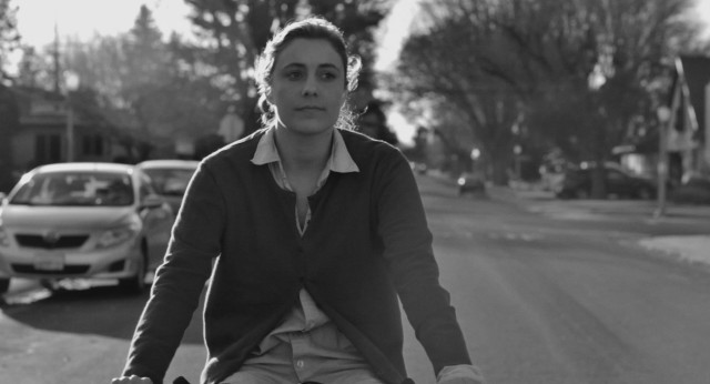 "Back home in Sacramento for Christmas, Frances Halladay (Greta Gerwig) enjoys a bike ride around the old neighborhood in ""Frances Ha."""