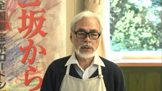 An apron-clad Hayao Miyazaki gives a production update at a press conference following the 2011 Tohoku Earthquake.