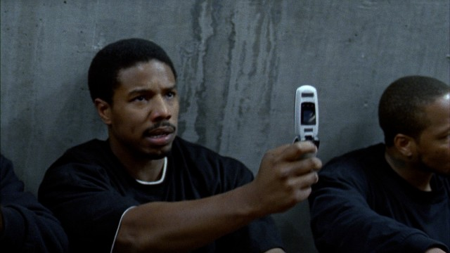 Oscar Grant (Michael B. Jordan) tries to use his cell phone while being detained on the Frutivale Station platform in the early morning hours of New Year's Day 2009.