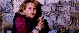 A chained-up Abby (Mae Whitman) has cartoons projected on her in the killer's dungeon of doom.