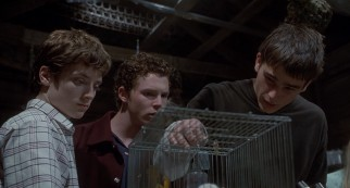 Zeke (Josh Hartnett) runs tests on a mouse as Casey (Elijah Wood) and Stan (Shawn Hatosy) look on.
