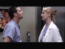 Izzie and Alex in front of...an elevator. Oooohhh.