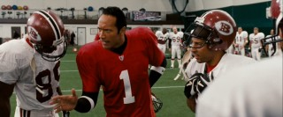 "In ""The Game Plan"", Dwayne ""The Rock"" Johnson plays Joe Kingman, an Elvis fan who's also star quarterback for the Boston Rebels."