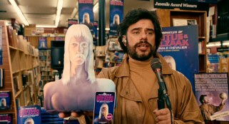 Bearded sci-fi author and artist Ronald Chevalier (Jemaine Clement) is in his element with a Brutus pillow in hand and hundreds of to-be-signed book copies around him.