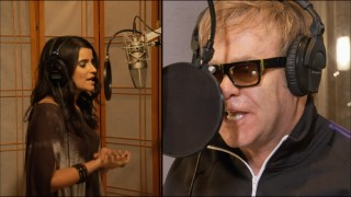 "Nelly Furtado and Elton John duet from a distance in their brief, lazy ""Crocodile Rock"" music video."