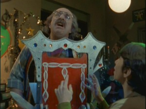 A horrified Tim watches as magic shop owner Mr. Malik (Harvey Atkin) has an accident with an unfortunately-placed guillotine.