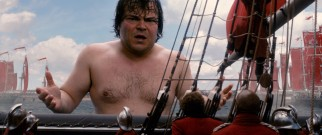 A wet, shirtless Gulliver (Jack Black) encourages the Blefuscian Armada to retreat in response to his antics.