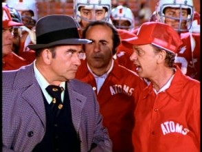 Hank (Ed Asner) glares at Coach Venner (Don Knotts).