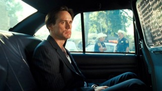 Beat but not beaten, Steven Russell (Jim Carrey) plans his next move from the back seat of a police car.