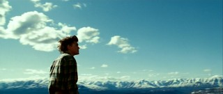 Snowy mountains and cotton clouds are witnessed by both the movie's protagonist and the viewer in this sweeping panoramic shot.