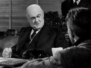 Mr. Potter (Lionel Barrymore) wears a scowl while reveling in the opportunity to deny George assistance.