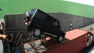 "A jeep drives onto a truck on tracks and in front of green screen in ""Anatomy of a Car Chase."""