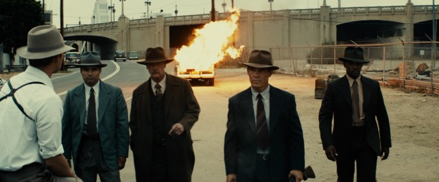 The Gangster Squad walks calmly and coolly away from an exploded car.