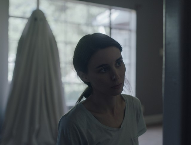 The ghost (Casey Affleck) looks on as his widow (Rooney Mara) grieves in the house they shared.