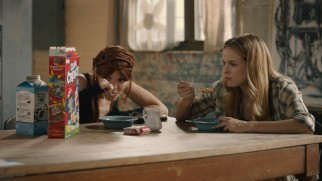 Lu (Nicole LaLiberte) and Shae (Danielle Panabaker) marvel at the nutritional value of Cap'n Crunch.