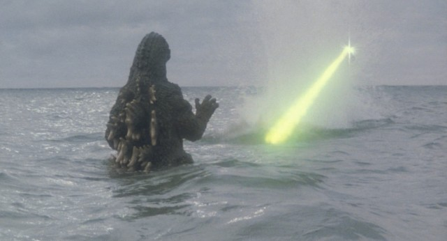 Godzilla makes an aquatic return from Mt. Mihara and is greeted by the green light of military aircraft fire.