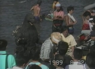 "A rather human-sized Godzilla is seen hanging out in the water with crew members during the making of ""Godzilla vs. Biollante."""