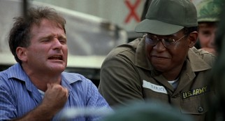 Cronauer (Robin Williams) does his impression of a newswire to the amusement of his assistant (Forest Whitaker) and other American troops.