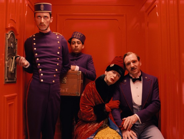 Madame D (Tilda Swinton) lays her head on M. Gustave's (Ralph Fiennes) shoulder as they take a colorful elevator ride down The Grand Budapest Hotel.
