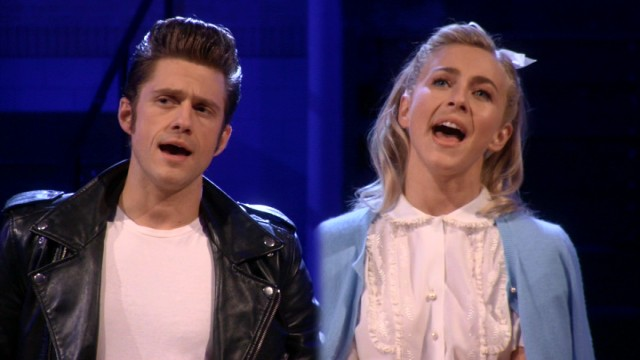 "Danny Zuko (Aaron Tveit) and Sandy Young (Julianne Hough) sing of their shared summer romance to their respective cliques in ""Grease Live!"""