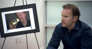 Morgan Spurlock pitches movie sponsorship to Ban, as a photo behind him reveals the kind of advertising he is willing to do.