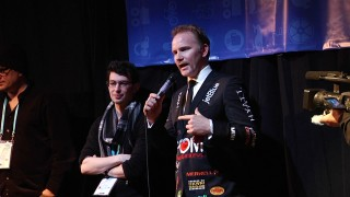 Documentarian Morgan Spurlock answers audio questions at the 2011 Sundance Film Festival, where his jacket advertises the film's promotional partners.