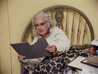 "From bed, Edith ""Big Edie"" Beale looks at old pictures in a folder Little Edie has just ripped trying to take from her."